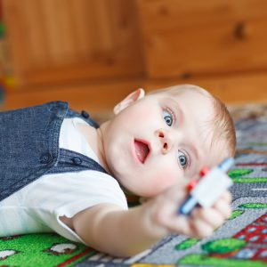 Lovely baby boy playing with toys at home. Cute funny child having fun with playing. Kid development concept.